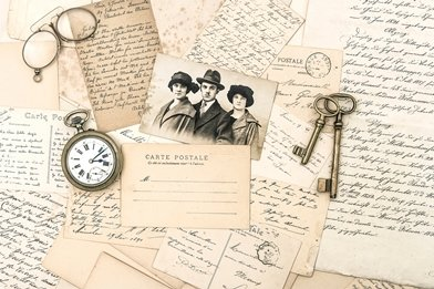 Old French handwritten notes and postcards with keys, a photograph, pocket watch and spectacles