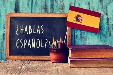 Hablas Espanol written on blackboard with Spanish flag