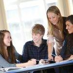 Tutor helping 3 students at desk with studies