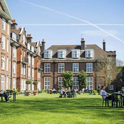 Regent's University London building exterior with students sitting at tables in the garden