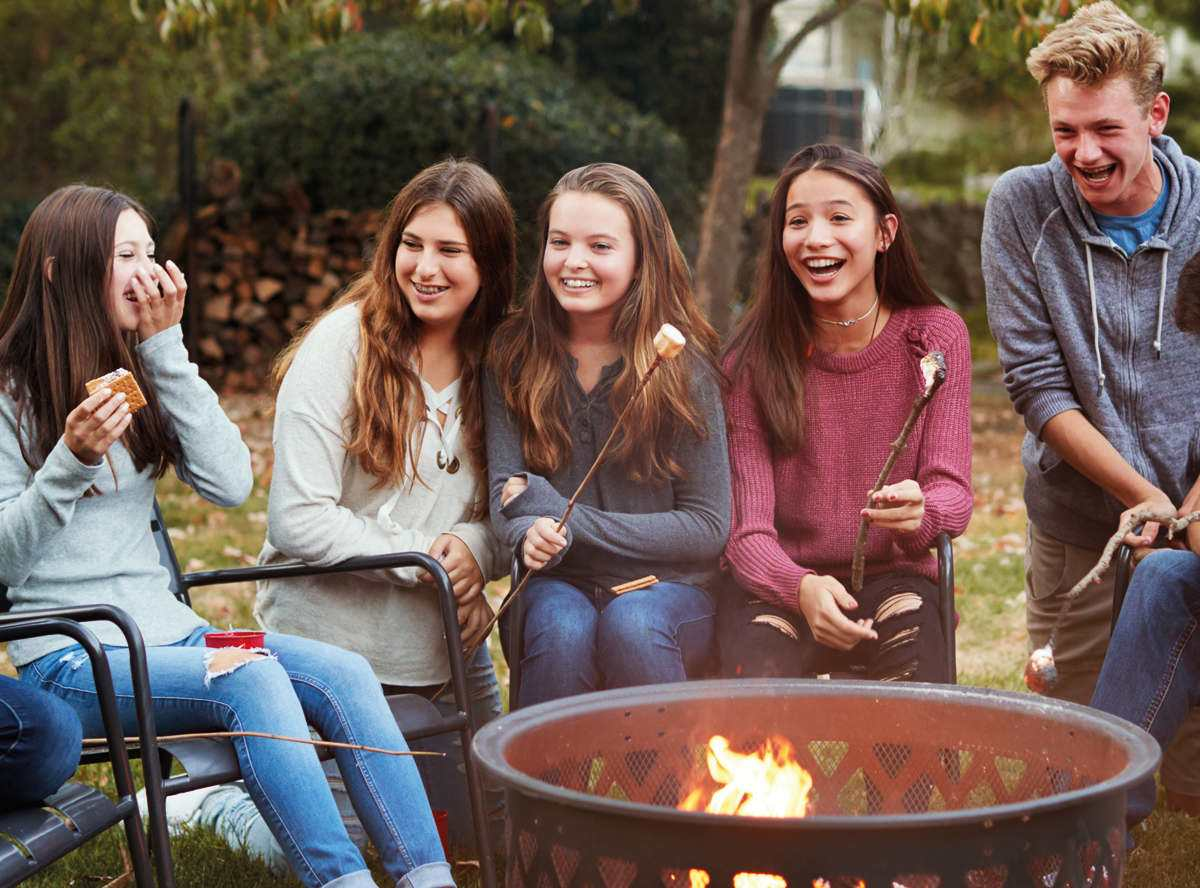 Students laughing while eating smores around a firepit